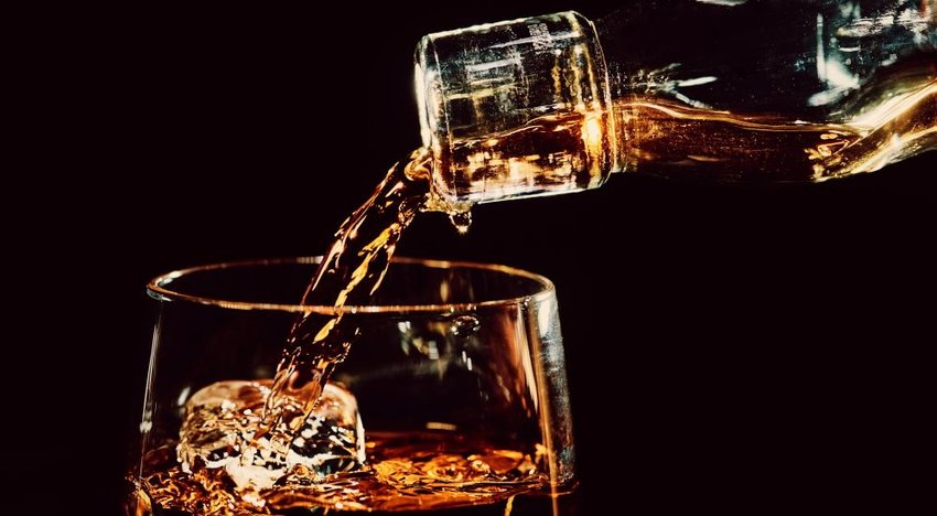 Bourbon pouring out of a bottle into a glass with ice