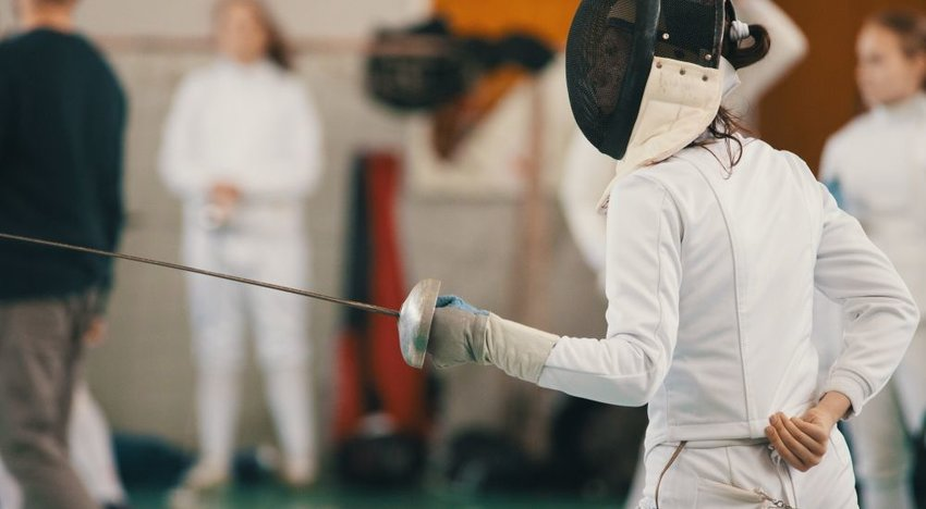 A person holding a sword for a fencing competition