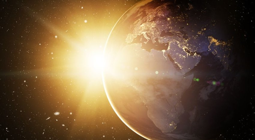 The sun rising above Earth in outer space