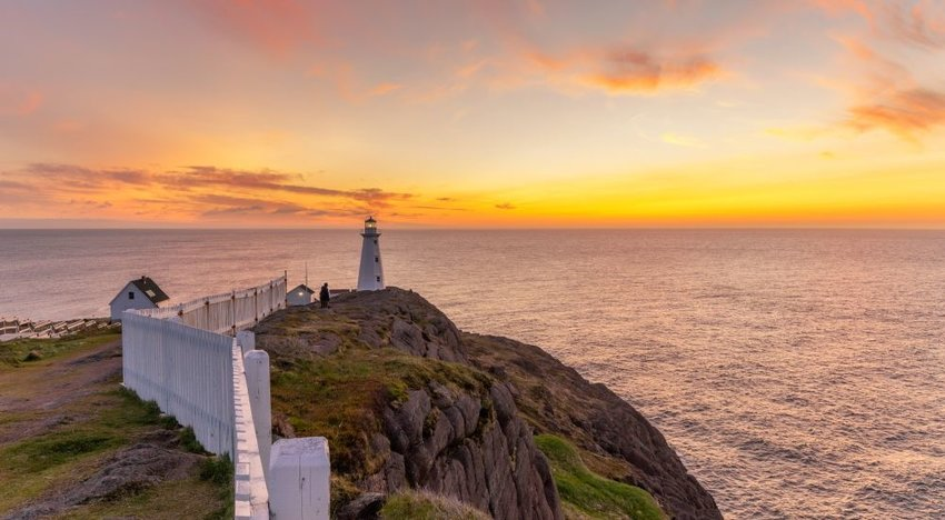 A lighthouse on a cliffside overlooking a sunset over the ocean