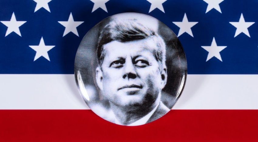 A photo of John F. Kennedy in front of an American flag