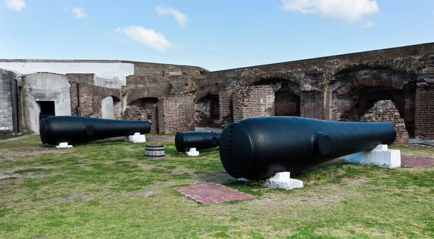 Photo of old cannons in front of a crumbling brick wall