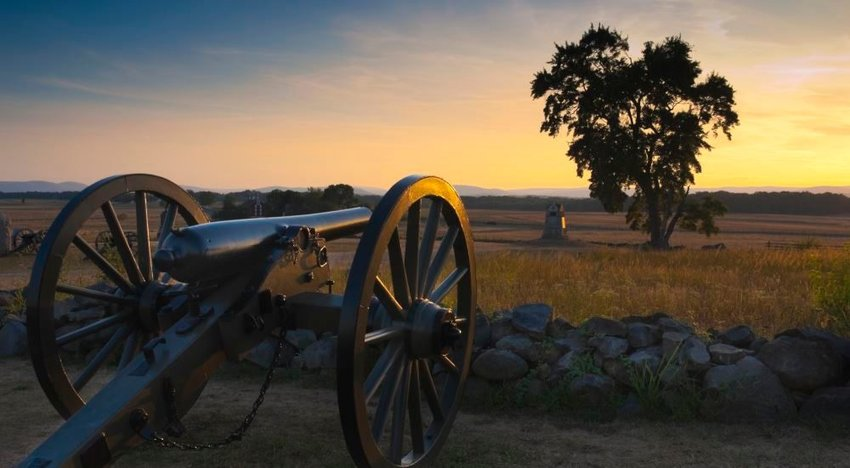 Photo of an old Civil War canon on a field at sunset