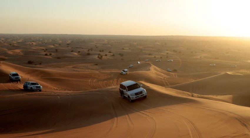 Photo of a vast desert with cars driving up sand dunes