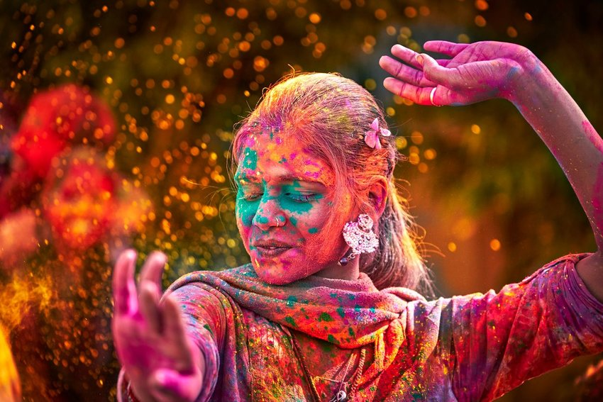 Woman covered in gulal (colorful powder), dancing