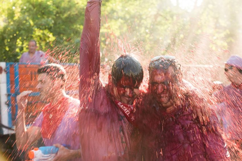 Men getting soaked with red wine from above