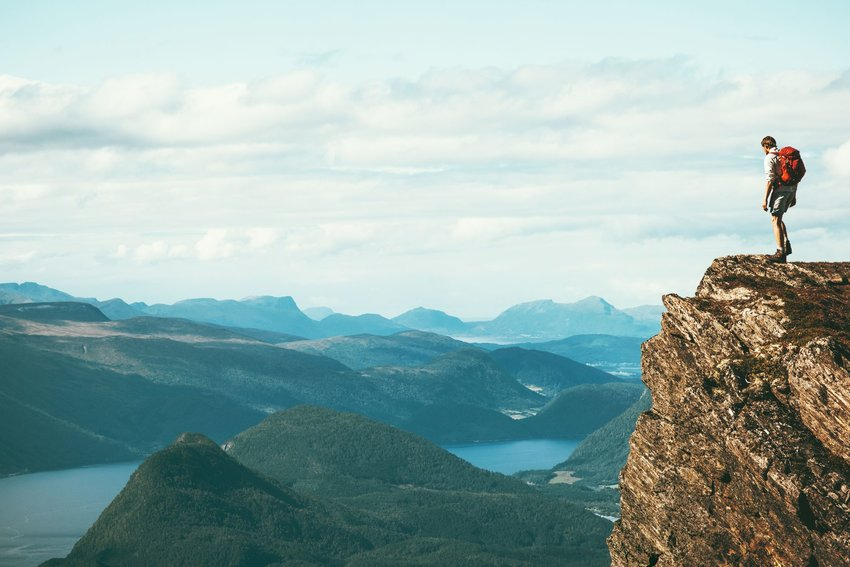 Person on a cliff overlooking mountains and a lake