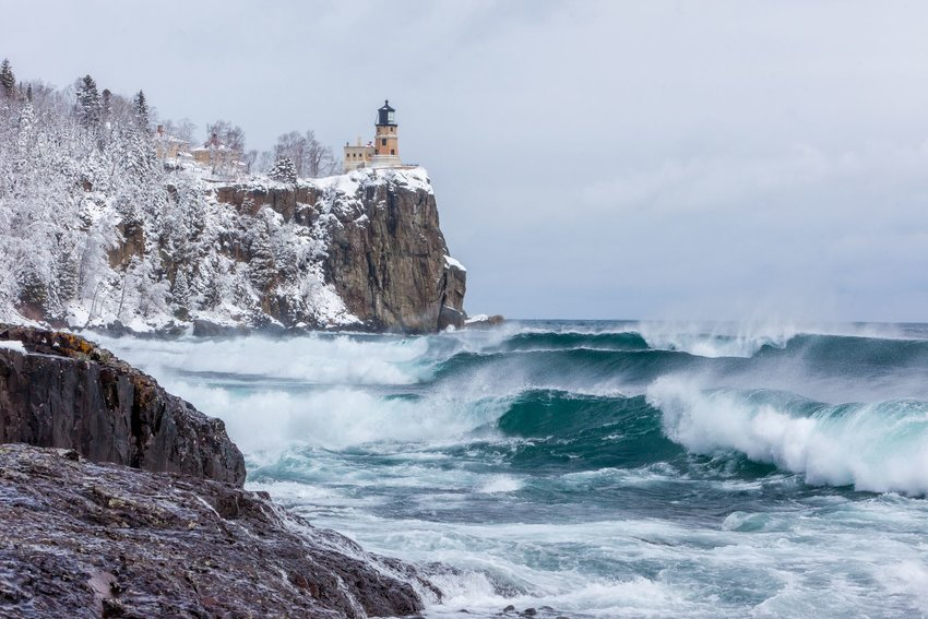 Photo of Lake Superior in winter with a lighthouse in the background