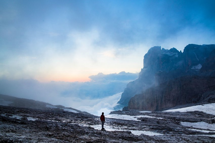 Solo hiker on a snowy slope in Italy