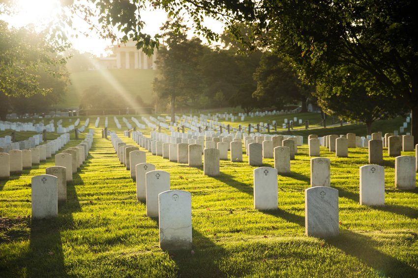 Rows of tombstones with sunlight filtering through them at Arlington National Cemetery in the United States