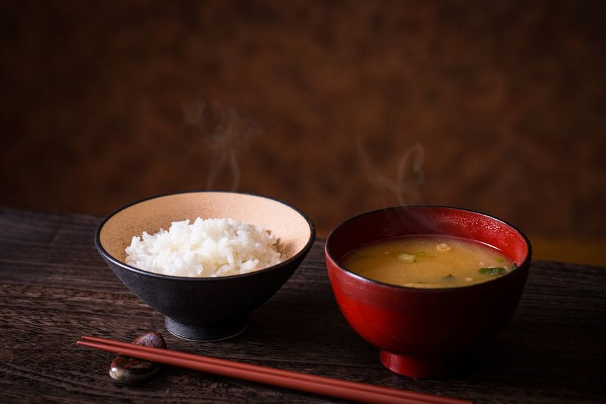 Chopsticks set on an utensil holder next to a bowl of rice and a bowl of miso soup