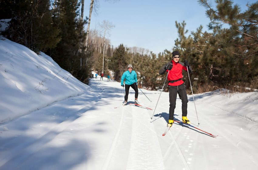 Couple cross-country skiing down a wide snowy path in Minnesota