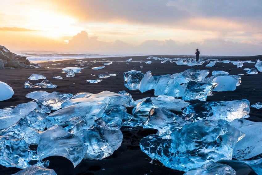 Diamond Beach in Iceland with blue icebergs melting on the black sand