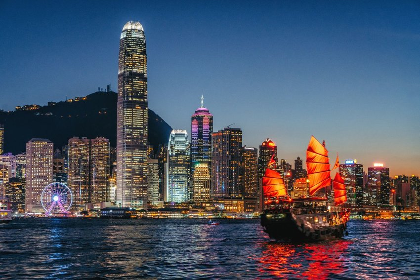 A junk sailing on the waters set against the Hong Kong city skyline