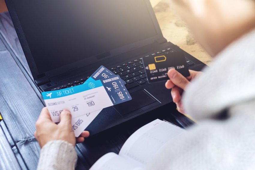 A man holding two plane tickets in his left hand and a credit card in his right hand