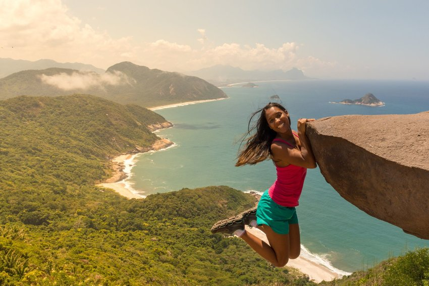 Young woman appearing to hang off on the edge of Pedra do Telegrafo