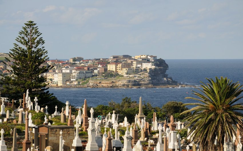 View of the harbor past tombstones in Waverley Cemetery in Sydney, Australia