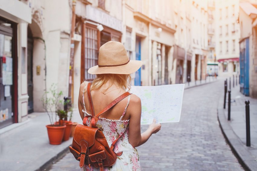 woman with a backpack and map in European alleyway