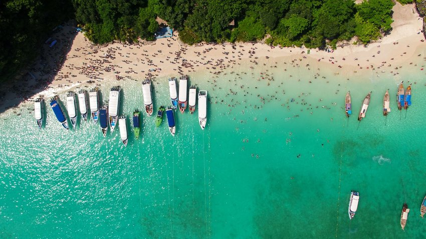Aerial photo of boats near shore in Maya Bay, Thailand