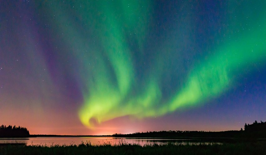Multicolor sky with northern lights over a lake