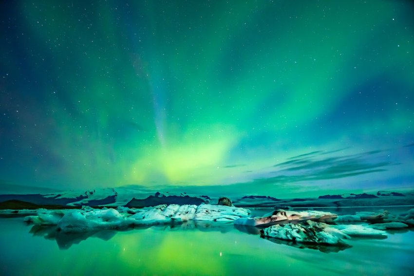 Green and blue northern lights over small glaciers