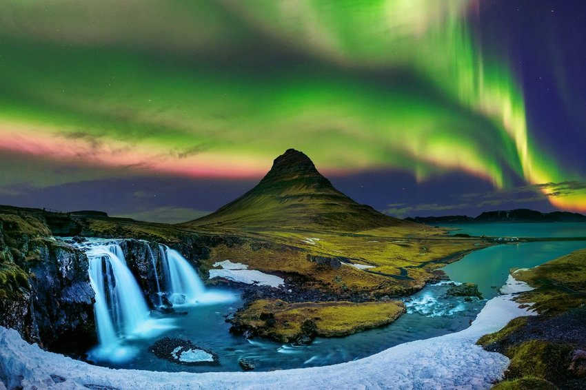 Waterfall and mountain peak with northern lights in the background