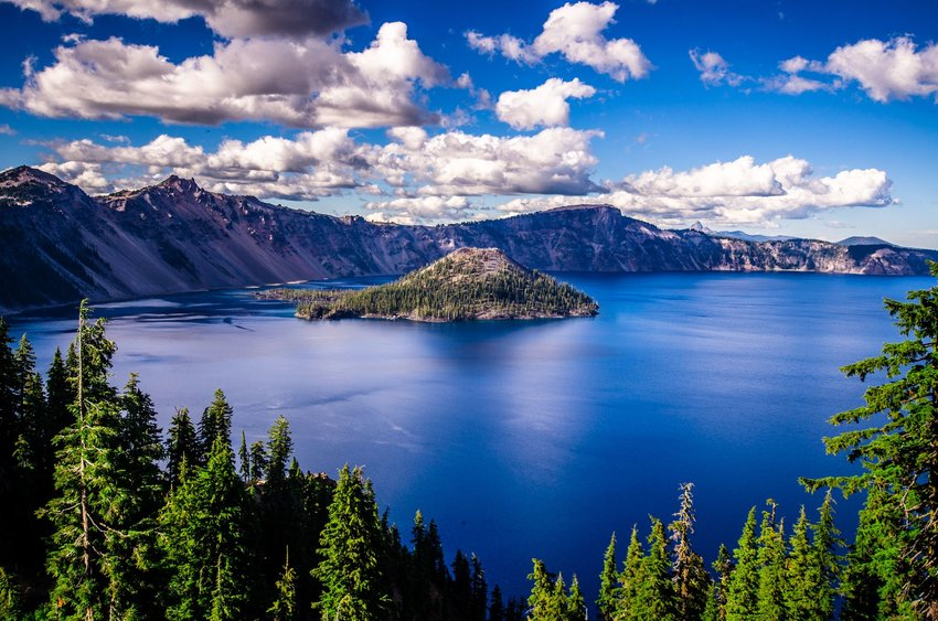 Crater Lake, Oregon, behind a forest and with mountains in the background