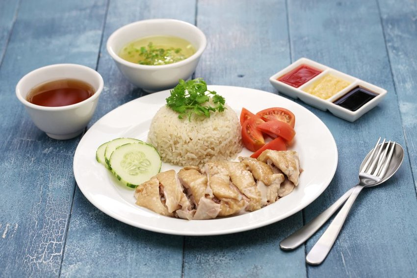 Hainanese chicken rice with tomatoes, cucumbers, chicken broth, and condiments