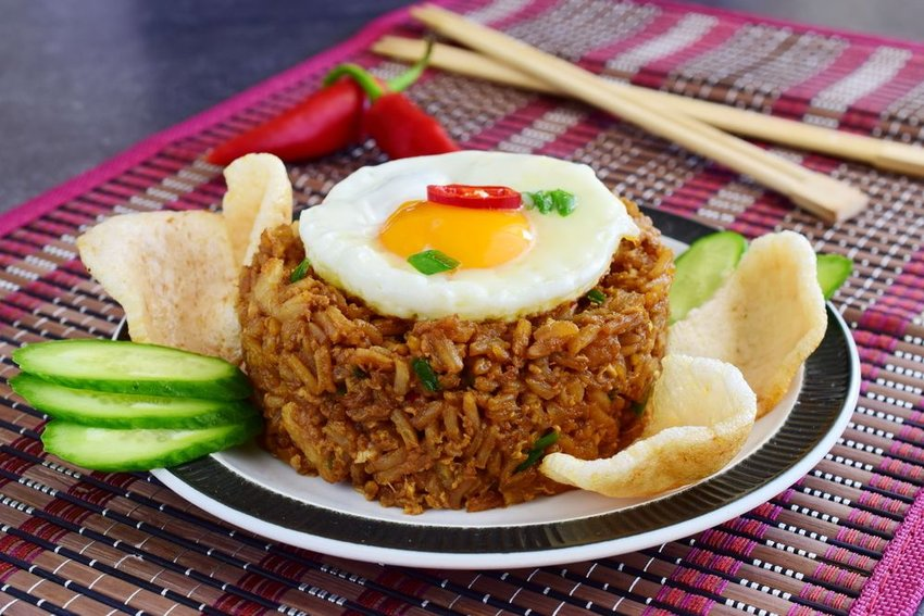 Nasi goreng or Indonesian fried rice with shrimp crackers and cucumber slices
