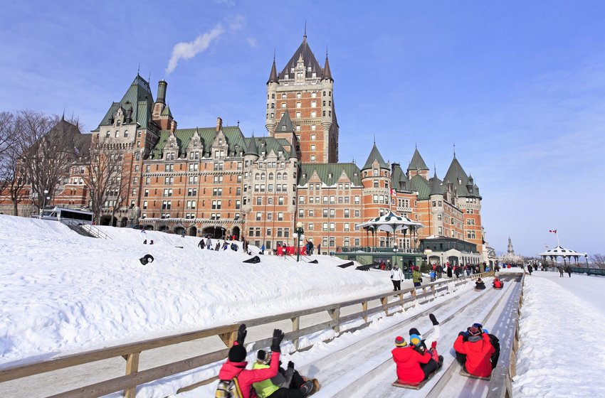 People sliding down the snow in front of Chateau Frontenac, Quebec City
