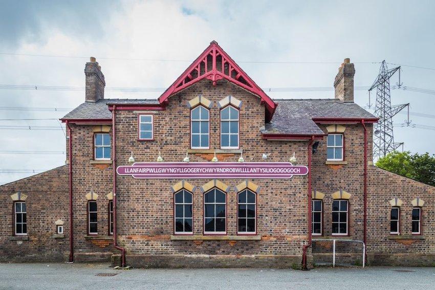 """Railway station with a sign reading """"Llanfairpwllgwyngyllgogerychwyrndrobwllllantysiliogogogoch"""""""