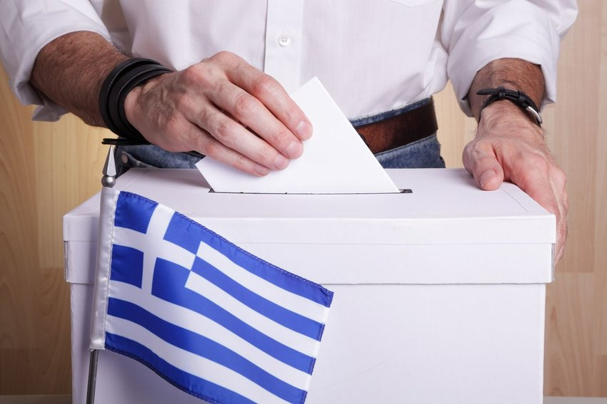 Man casting a vote into a white box with a Greek flag in front