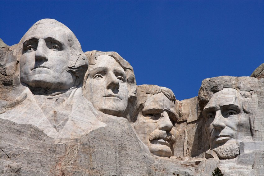 Close-up of the carved presidential faces on Mount Rushmore on a sunny, cloudless day.
