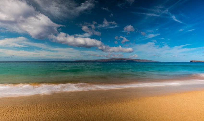 Kaho'olawe island seen from Makena Beach in Hawaii under a blue sky with clouds.