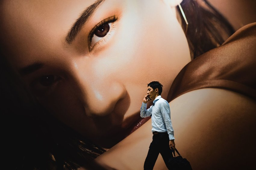 Man talking on phone while walking at Shiodome Station, Minato-ku, Japan