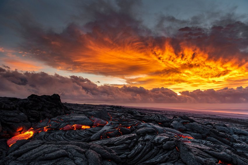 Glowing lava flows over black rock against a brilliant orange and yellow sunset on Kilauea volcano.