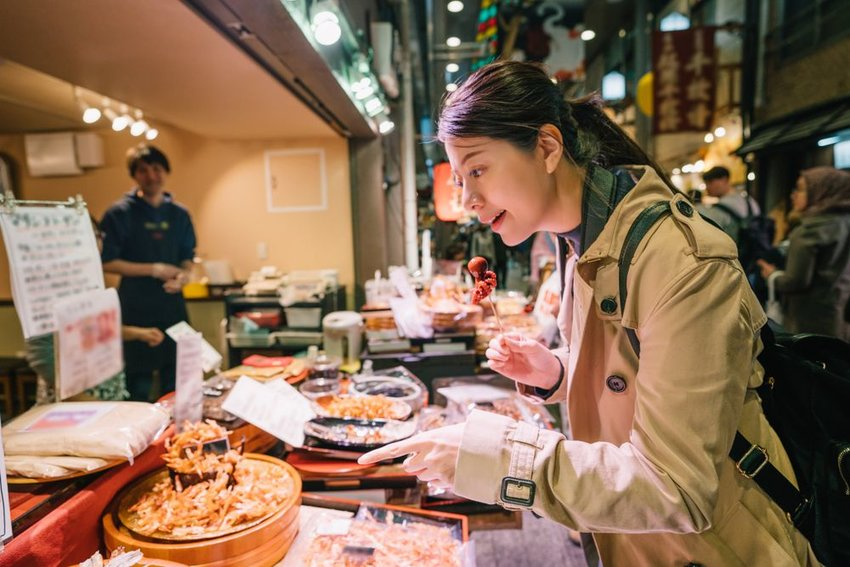 Tourist pointing at Japanese street food