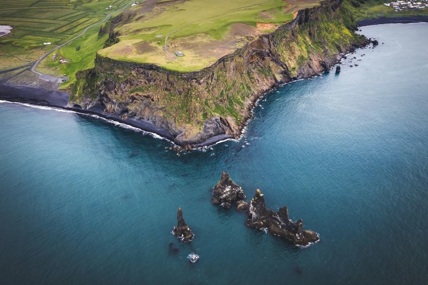 Aerial landscape photo of Atlantic Ocean meeting the coast of Iceland