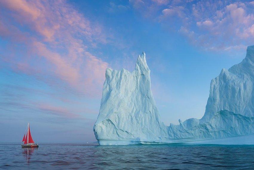 Little red sailboat cruising among floating icebergs in Disko Bay
