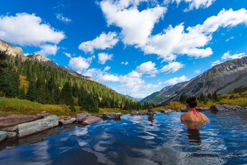Woman in hot spring in Aspen, Colorado with mountainous view in the background