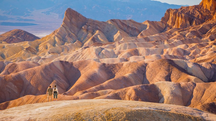 Two hikers standing in front of the Zabriskie Point overlook rock formation in Death Valley, California.