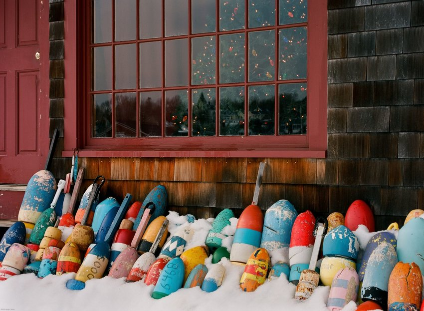 A pile of colorful lobster buoys stacked against a building in the snow with a Christmas tree in the window.