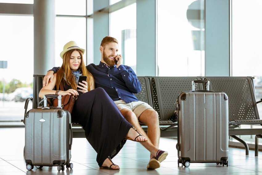 A couple using cell phones in an airport lounge