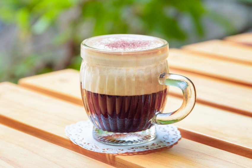 A frothy cup of ca phe trung on a slatted wooden table