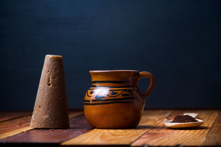 A clay pot of coffee next to a cone of piloncillo and a spoonful of spices on a wooden table