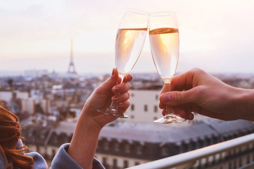 A French couple making a toast, with the Eiffel Tower in the background