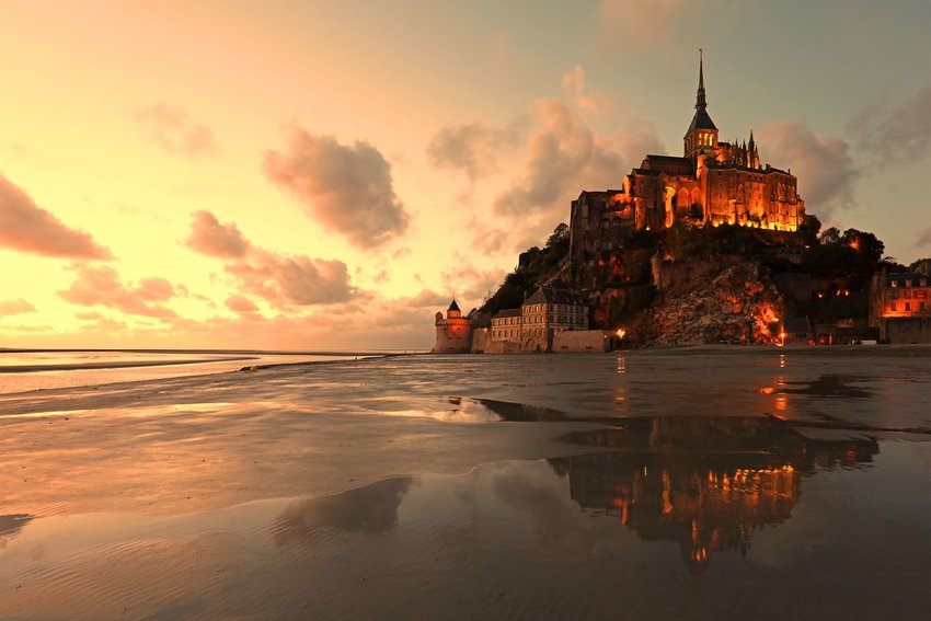 The buildings and the abbey of Mont Saint-Michel are lit at sunset on a summer evening