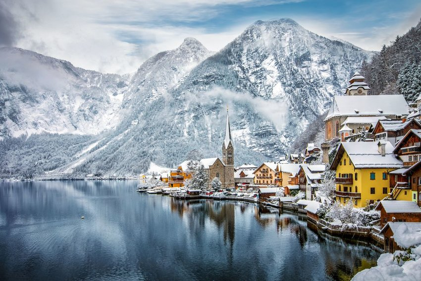 Village of Hallstat, Austria covered in snow with lake and mountains in the background