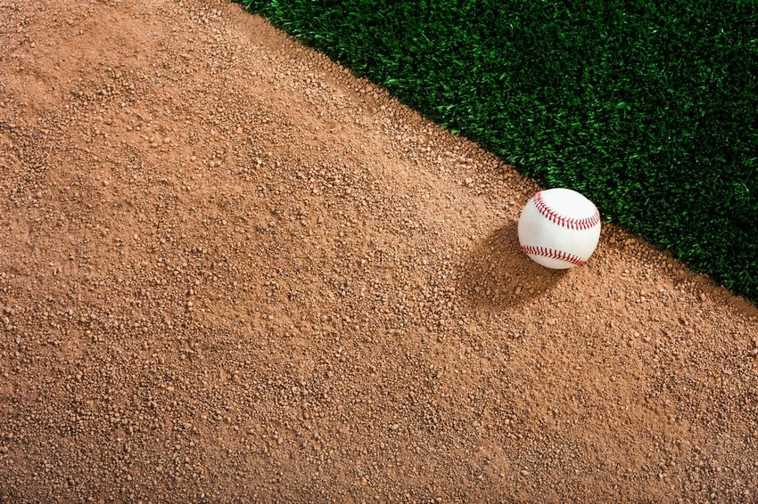 A single baseball sitting in the dirt