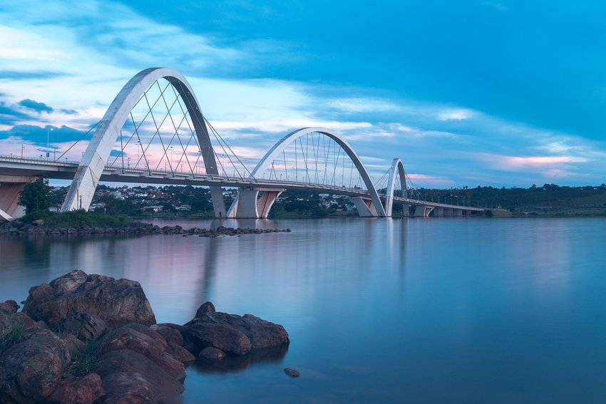 A blue and pink sunset view over a modern white bridge in Brasilia